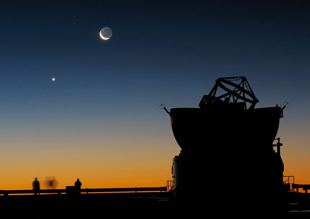 1024px-Sunset_view_at_Paranal_with_Moon,_Venus_and_an_AT.jpg